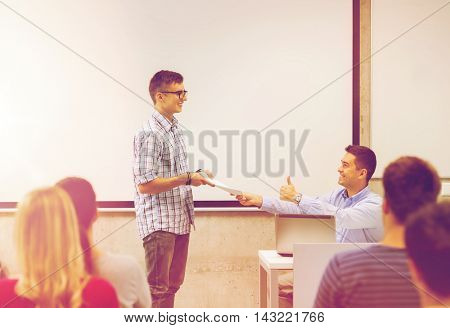 education, high school, technology and people concept - smiling student with notepad, laptop computer standing in front of teacher showing thumbs up gesture in classroom