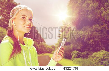 fitness, sport, training, technology and exercising concept - sporty woman with smartphone and earphones listening to music outdoors over road and natural background