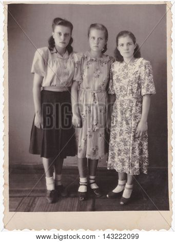 VITEBSK BELARUS - CIRCA 1955: Group portrait of three girlfriends in full growth (vintage black and white photo 1950s)