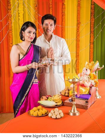 good looking Indian young couple performing puja in front of lord ganesh on ganesh festival or ganesh utsav or ganpati festival