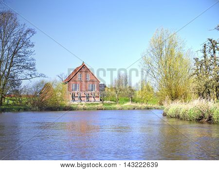 House at a river, spring scene at a riverside.