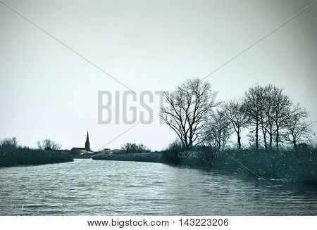 River scene in winter with bare trees and church tower in tae background. Turquoise colored image with copy space.
