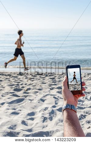A businessman photographing a guy at the beach on vacation.