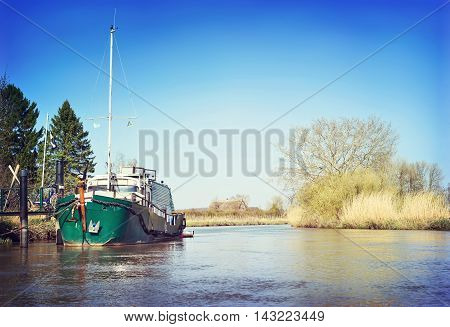 Sunny riverside scene with anchored sailing ship at a pier. Springtime.