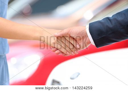 Car sale concept. Customer and salesman shaking hands.