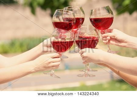 Female hands clinking glasses with red wine, outdoors