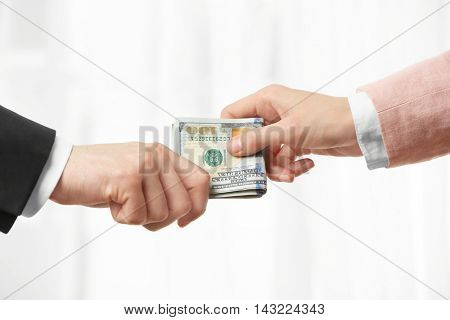 Man in suit taking bribe from woman hand closeup