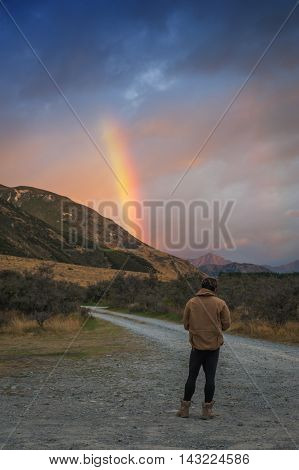 Man looking at rainbow over mountain near Lake Pearson / Moana Rua Wildlife Refuge located in Craigieburn Forest Park in Canterbury region South Island of New Zealand