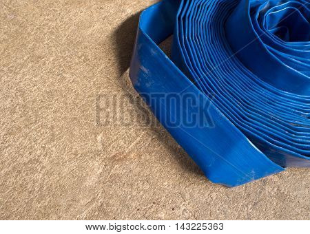 Blue canvas hose rolled on the concrete floor
