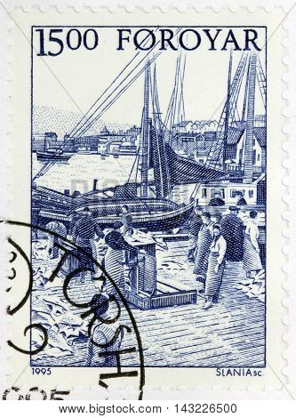 LUGA RUSSIA - JUNE 25 2016: A stamp printed by FAROE ISLANDS shows schooners at harbor saltfish being brought ashore circa 1995.