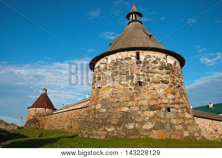 Ancient monastery tower against the blue sky. Architecture exterior