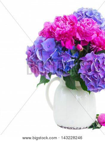 Bright pink peony, eustoma and blue hortensia fresh flowers bouquet in vase close up isolated on white background