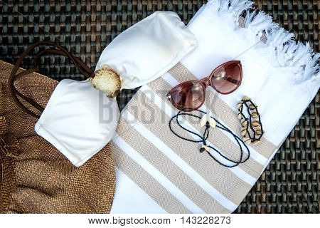 Concept of flat lay summer accessories of white and beige Turkish towel, sunglass, straw hat, white bikini top, white seashell bracelet and shark tooth necklace on rattan lounger.