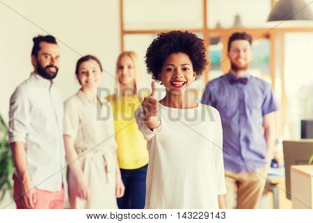 business, startup, people, gesture and teamwork concept - happy young african woman showing thumbs up over international creative team in office