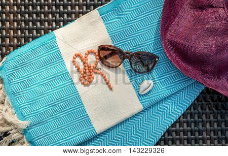 Concept of flat lay summer accessories of white and blue Turkish towel, sunglass, orange necklace, white seashell and straw hat on rattan lounger.