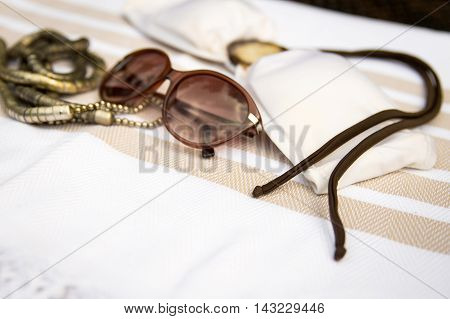 Concept of summer accessories of white and beige Turkish towel, sunglass, white bikini top and necklace on rattan lounger.