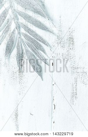 Silver fern leaf on a white wooden surface