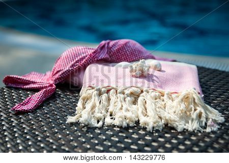 Concept of summer accessories close-up of white and ping Turkish towel, bikini top and white seashells on rattan lounger with blue swimming pool as background.