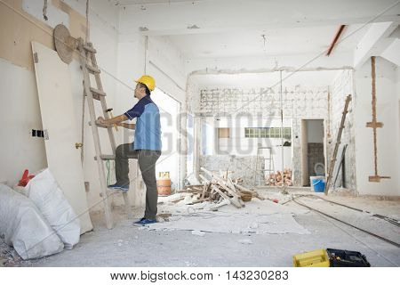 Asian construction worker with hardhat climbing up ladder at site, house renovation.