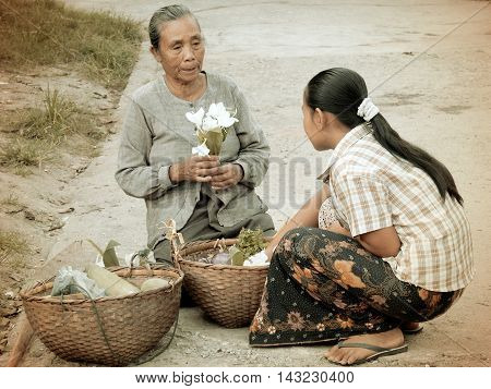 LUANG PRABANG LAO PDR - June 15 2004: A street vendor selling flowers to her customer in Luang Prabang Lao PDR in the old days