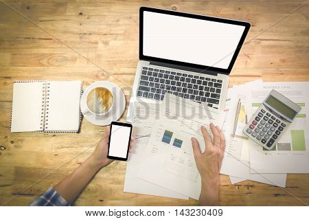 A man hand holding smart phone and discussing on stockmarket charts on wood desk in office with vintage effect.