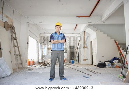 Asian construction worker with hardhat standing at site, house improvement concept.