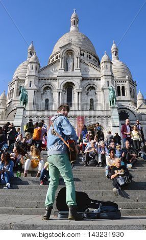 PARIS FRANCE - 20 APRIL 2015: Tourists visiting the Basilica of the Sacred Heart of Paris a Roman Catholic church and minor basilica located at the summit of the butte Montmartre the highest point of Paris