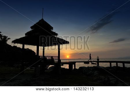 a tropical-style pavilion by the beach on an island in the Gulf of Thailand during sunset