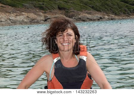Woman Wearing In Orange Life Jacket Looks At The Sea
