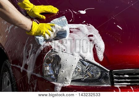 red car is washing in soap suds
