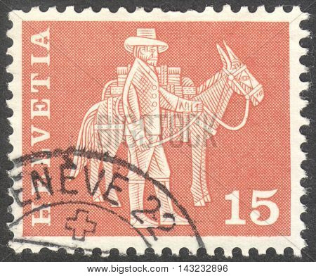 MOSCOW RUSSIA - CIRCA JUNE 2016: a post stamp printed in SWITZERLAND shows a man with a mule circa 1963.