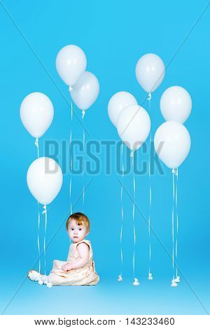 Adorable little baby sitting among white balloons over blue background. Infant baby. Healthcare. Happy childhood.
