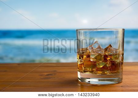 Glass of whisky with ice on a wooden table with a tranquil sea background