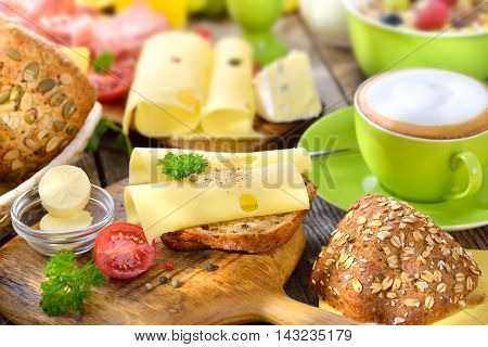 Hearty breakfast with a cup of cappuccino, cheese rolls and a large selection of food