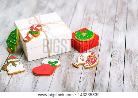 Christmas gift box with gingerbread cookies on white wooden background. Winter holidays concept. Space for text.