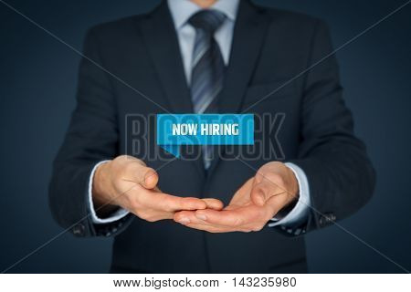 Now hiring - human resources concept. Businessman (recruiter HR staffer) hold virtual label with text now hiring.