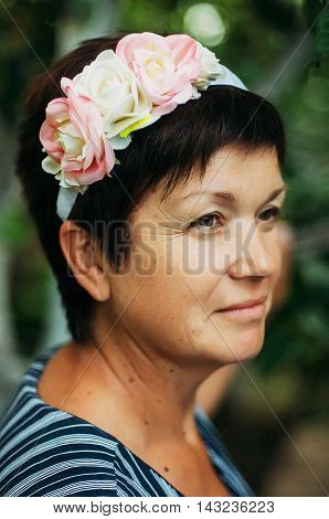 A portrait of a middle age woman. Portrait of a beautiful woman 55 years old posing on the rim of the beautiful Silk flowers outdoors