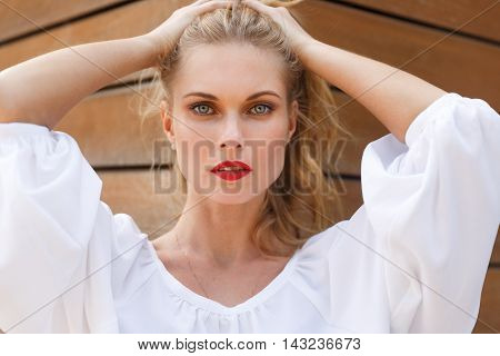 Gorgeous blonde woman with natural makeup and red lips in white blouse. Portrait on background of wooden wall