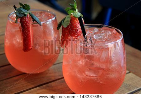 Two thirst-quenching Summertime drinks, with strawberries perched on the rim