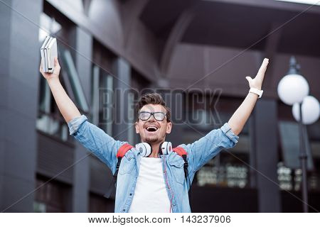 Express yourself. Overjoyed delighted smiling man holding hands up and holding books while standing near building