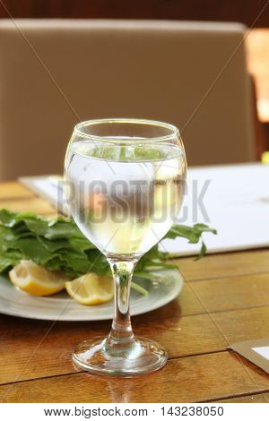 Glass of cold water next to lemon and greens. Served table