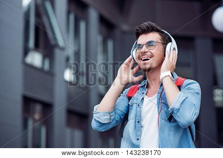 Feel the beat. Cheerful delighted smiling man holding his headphones and listening to music while standing near the building