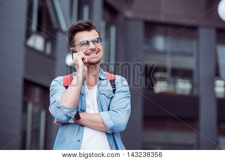 Nice to hear you. Cheerful handsome young man talking on cell phone and standing in the street while expressing joy