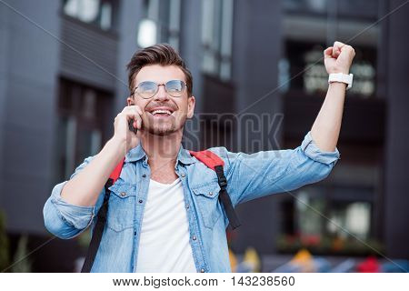 What a good news. Overjoyed delighted smiling hand holding hand up and talking on cell phone while expressing gladness