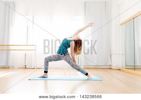 Graceful, flexible young woman practicing high lunge pose in light spacious yoga studio