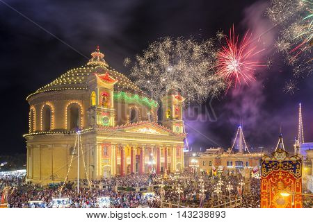 MOSTA MALTA - 15 AUG. 2016: Fireworks at the Mosta festival at night with the famous Mosta Dome and the People of Malta are celebrating the Feast of the Assumption of 'Santa Maria'.