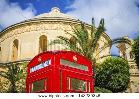 Mosta, Malta - Traditional British red telephone box with palm trees and the famous Mosta Dome at background