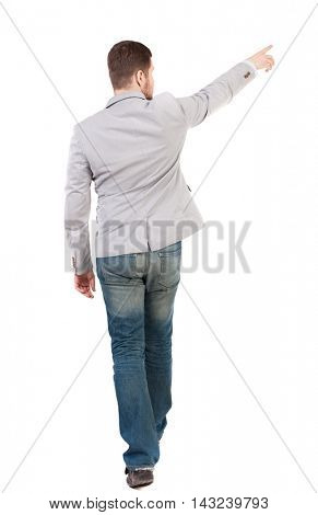Back view of going  business man pointing. walking young guy . Rear view people collection.  backside view of person.  Isolated over white background. A man in a gray jacket leaves the frame showing a