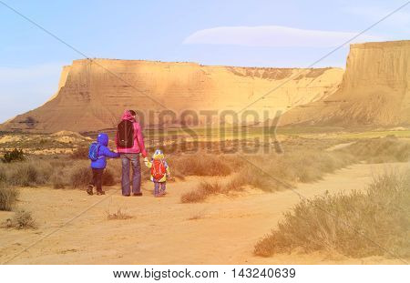 mother with little son and daugther hiking in scenic mountains, family travel