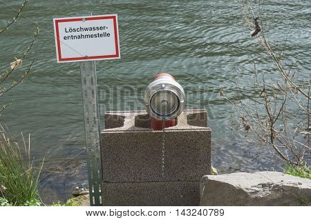 Information board with the inscription in German fire water extraction point. Firefighting Equipment in a river.
